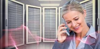Immagine composita della donna di affari sorridente che per mezzo del telefono cellulare immagini stock