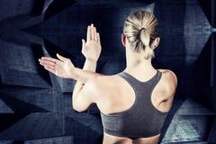 Immagine composita della donna muscolare con le armi attraversate Fotografia Stock