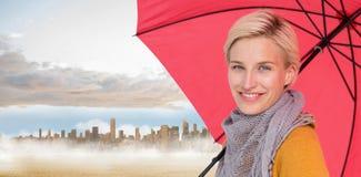 Immagine composita della donna sorridente che tiene un ombrello Fotografia Stock