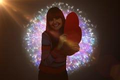 Immagine composita della donna sorridente dei pantaloni a vita bassa che tiene un cuore rosso Immagini Stock Libere da Diritti