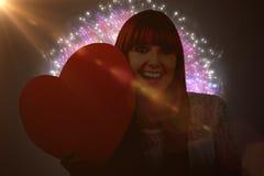 Immagine composita della donna sorridente dei pantaloni a vita bassa con un grande cuore rosso Fotografia Stock