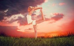 Immagine composita della donna sportiva che allunga corpo mentre equilibrando su una gamba Fotografie Stock Libere da Diritti