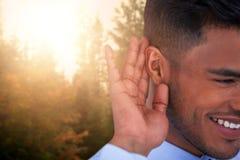 Immagine composita della fine su dell'uomo d'affari sorridente che prova ad ascoltare Fotografia Stock