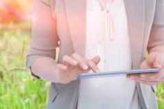Immagine composita della fine su della donna che per mezzo della compressa contro il paesaggio verde Fotografia Stock Libera da Diritti
