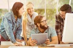 Immagine composita della gente di affari felice che per mezzo della compressa digitale allo scrittorio del computer fotografie stock libere da diritti