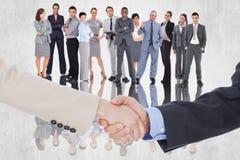Immagine composita della gente di affari sorridente che stringe le mani mentre esaminando la macchina fotografica Fotografia Stock Libera da Diritti