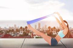 Immagine composita della giovane donna di misura che si esercita con una cinghia blu di yoga Fotografia Stock Libera da Diritti