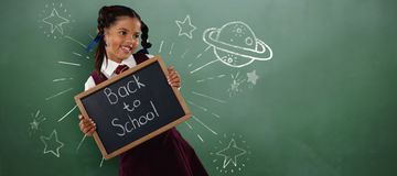 Immagine composita della lavagnetta sorridente della tenuta della scolara Fotografia Stock