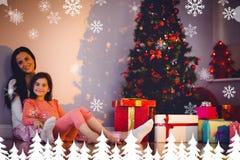Immagine composita della madre e della figlia il Babbo Natale aspettante Fotografie Stock Libere da Diritti