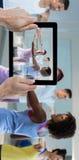 Immagine composita della mano potata che tiene compressa digitale Fotografia Stock