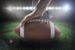 Immagine composita della palla 3D della tenuta del giocatore di football americano fotografia stock libera da diritti