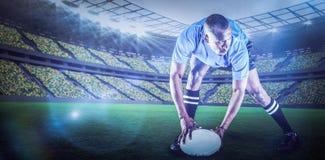 Immagine composita della palla della tenuta del giocatore di rugby mentre giocando con 3d Immagini Stock