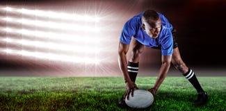 Immagine composita della palla della tenuta del giocatore di rugby mentre giocare e 3d Fotografia Stock Libera da Diritti