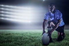 Immagine composita della palla della tenuta del giocatore di rugby mentre inginocchiarsi e 3d Immagine Stock Libera da Diritti
