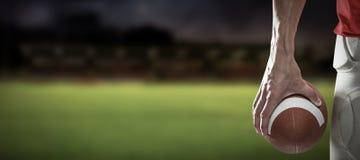 Immagine composita della palla della tenuta del giocatore di sport Immagine Stock