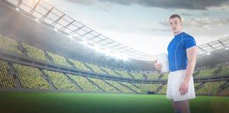Immagine composita della palla di rugby della tenuta del giocatore di rugby 3D Immagini Stock Libere da Diritti