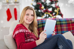 Immagine composita della ragazza graziosa che si trova sul sofà facendo uso della sua compressa che sorride alla macchina fotogra Fotografia Stock