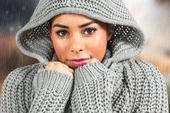 Immagine composita della ragazza graziosa nel saltatore di inverno che esamina macchina fotografica fotografia stock