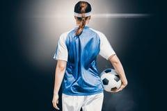 Immagine composita della retrovisione del calciatore della donna che tiene una palla immagine stock libera da diritti