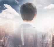 Immagine composita della retrovisione dell'uomo d'affari che guarda attraverso la finestra di costruzione del 3d Fotografie Stock