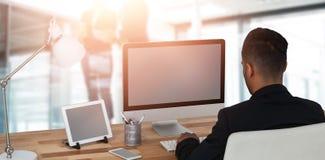 Immagine composita della retrovisione dell'uomo d'affari che lavora sopra il computer fotografie stock libere da diritti