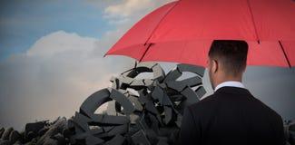 Immagine composita della retrovisione dell'uomo d'affari che porta ombrello rosso Fotografia Stock