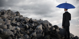 Immagine composita della retrovisione dell'uomo d'affari che tiene ombrello e cartella blu Immagine Stock Libera da Diritti