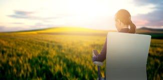 Immagine composita della retrovisione della donna di affari che usando cellulare mentre sedendosi sulla sedia Immagine Stock Libera da Diritti