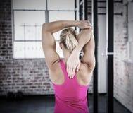 Immagine composita della retrovisione della donna muscolare che allunga il suo braccio Fotografie Stock