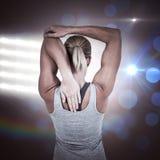 Immagine composita della retrovisione della donna muscolare che allunga il suo braccio Fotografia Stock