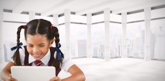 Immagine composita della scolara che per mezzo della compressa digitale allo scrittorio immagine stock