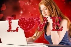 Immagine composita della testarossa graziosa che lavora al computer portatile Immagini Stock Libere da Diritti