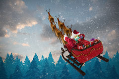 Immagine composita della vista dell'angolo alto della guida del Babbo Natale sulla slitta con il contenitore di regalo Immagini Stock
