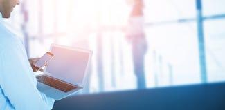 Immagine composita della vista laterale dell'uomo d'affari facendo uso del telefono cellulare e del computer portatile Immagini Stock Libere da Diritti