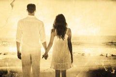 Immagine composita delle coppie attraenti che si tengono per mano e che guardano l'oceano Fotografie Stock Libere da Diritti