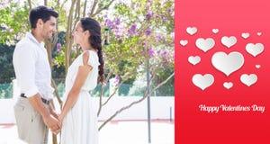 Immagine composita delle coppie attraenti che stanno nel tenersi per mano del giardino Fotografia Stock Libera da Diritti