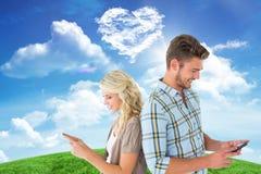 Immagine composita delle coppie attraenti facendo uso dei loro smartphones Fotografia Stock Libera da Diritti