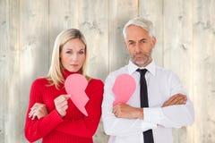 Immagine composita delle coppie che non parlano le metà della tenuta due di cuore rotto Fotografia Stock Libera da Diritti