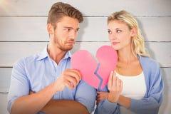 Immagine composita delle coppie che tengono due metà di cuore rotto Immagine Stock