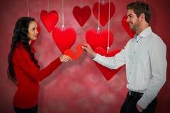 Immagine composita delle coppie che tengono forma incrinata rossa 3d del cuore Fotografie Stock Libere da Diritti
