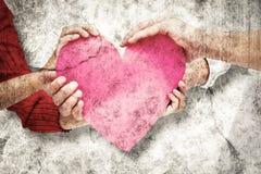 Immagine composita delle coppie che tengono un cuore Fotografia Stock Libera da Diritti