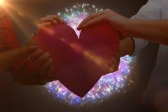 Immagine composita delle coppie che tengono un cuore Fotografia Stock