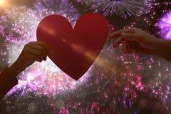 Immagine composita delle coppie che tengono un cuore Fotografie Stock