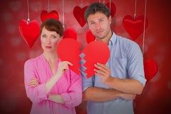 Immagine composita delle coppie che tengono un cuore rotto 3D Immagini Stock Libere da Diritti