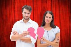 Immagine composita delle coppie di ribaltamento che tengono due metà di cuore rotto Fotografia Stock