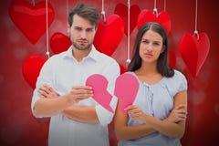 Immagine composita delle coppie di ribaltamento che tengono due metà di cuore rotto 3D Fotografia Stock Libera da Diritti