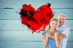 Immagine composita delle coppie felici che abbracciano e che tengono il rullo di pittura Fotografia Stock