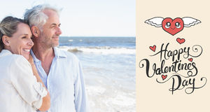 Immagine composita delle coppie felici che abbracciano sulla spiaggia che guarda fuori al mare Fotografie Stock