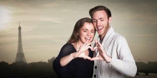 Immagine composita delle coppie felici che formano cuore con le mani Immagini Stock Libere da Diritti