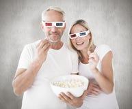 Immagine composita delle coppie felici che indossano i vetri 3d che mangiano popcorn Fotografia Stock